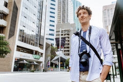 Male tourist in city. Happy male tourist in city walking with camera Royalty Free Stock Images