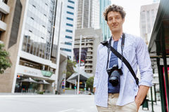 Male tourist in city. Happy male tourist in city walking with camera Stock Photo