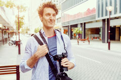 Male tourist in city. Happy male tourist walking in city with camera Stock Photo