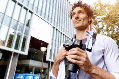 Male tourist in city. Happy male tourist walking in city with camera Stock Images