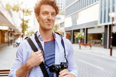 Male tourist in city. Happy male tourist walking in city with camera Royalty Free Stock Photo