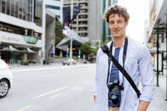 Male tourist in city. Happy male tourist in city walking with camera Royalty Free Stock Photos