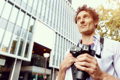 Male tourist in city. Happy male tourist walking in city with camera Royalty Free Stock Photos