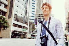 Male tourist in city. Happy male tourist in city walking with camera Stock Images