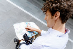 Male tourist in city. Young male tourist in city with camera and map Royalty Free Stock Image