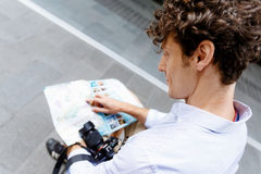Male tourist in city. Young male tourist in city with camera and map Royalty Free Stock Photos