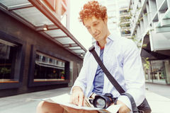 Male tourist in city. Young male tourist in city with camera and map Royalty Free Stock Photography