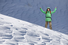 Male Tourist climber with arms upraised on the background of snowy mountain landscape. Gesture of success. Male Tourist climber with arms upraised on the Stock Image