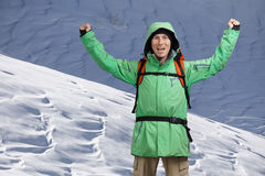 Male Tourist climber with arms upraised on the background of snowy mountain landscape. Gesture of success. Male Tourist climber with arms upraised on the Royalty Free Stock Photos