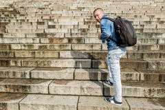 Male tourist climbs up the granite stairs. Male tourist with backpack climbs up the granite stairs Stock Photography