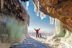 Male tourist with a dog near the ice grotto Olkhon Island on Lak. E Baikal, winter day Stock Images
