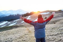 Male tourist enjoying beautiful panorama in the evening. Man with raised hands watching beautiful scenery in mountains during colorful sunset Stock Photo