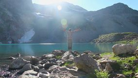 Male tourist enjoying freedom beautiful view near mountain lake. Stock footage stock footage