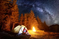 Male tourist enjoying in his camp near the forest at night under night sky full of stars and milky way. Astrophotography. Male tourist enjoying in his camp near royalty free stock image
