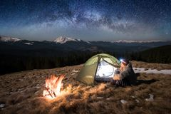Male tourist enjoying in his camp at night. Man with a headlamp under beautiful sky full of stars and milky way. Male tourist enjoying in his camp at night. Man Stock Photo