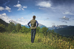 Male tourist enjoying the scenic Bavarian alps. Rear view of a male tourist standing on a grassy plateau enjoying the scenic Bavarian alps in the Berchtesgaden Stock Photography