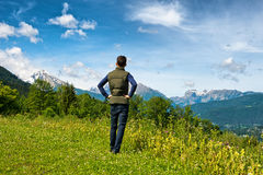 Male tourist enjoying the scenic Bavarian alps. Rear view of a male tourist standing on a grassy plateau enjoying the scenic Bavarian alps in the Berchtesgaden Stock Photo