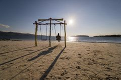 Male tourist enjoys sunset view on a swing stock photo