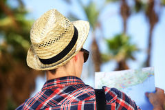 Male tourist with hat looking at map on vacation. Rear portrait of a male tourist with hat looking at map on vacation Stock Image