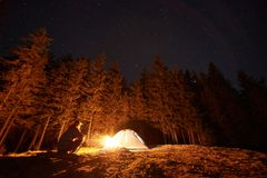 Male tourist have a rest in his camp near the forest at night Stock Photos