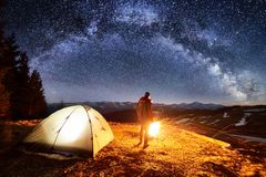 Male tourist have a rest in his camp near the forest at night. Man near campfire and tent under night sky full of stars Stock Photos