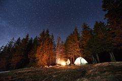 Male tourist have a rest in his camp near the forest at night under beautiful night sky full of stars Royalty Free Stock Photography