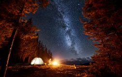 Male tourist have a rest in his camp near the forest at night under beautiful night sky full of stars and milky way Royalty Free Stock Image
