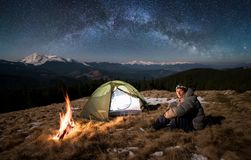 Male tourist have a rest in his camp at night under beautiful sky full of stars and milky way. Male tourist have a rest in his camp at night. Man sitting near Royalty Free Stock Image