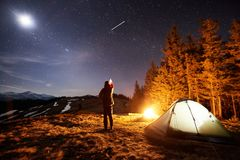 Male tourist have a rest in his camp at night under beautiful night sky full of stars and the moon. Male tourist have a rest in his camp at night. Man standing Royalty Free Stock Image