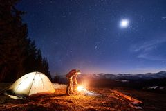 Male tourist have a rest in his camp at night under beautiful night sky full of stars and the moon. Male tourist have a rest in his camp at night near campfire Royalty Free Stock Photos