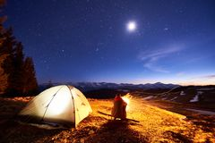 Male tourist have a rest in his camp at night near campfire and tent under night sky full of stars and the moon. Male tourist have a rest in his camp at night Stock Photography