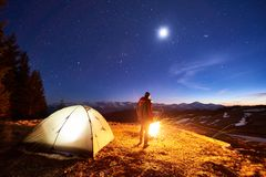 Male tourist have a rest in his camp at night, standing near campfire and tent under beautiful night sky full of stars. And the moon and enjoying night scene in Stock Image