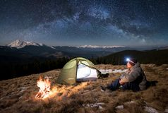 Male tourist have a rest in his camp at night under beautiful sky full of stars and milky way. Male tourist have a rest in his camp at night. Guy with a headlamp Royalty Free Stock Photography