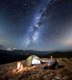 Male tourist have a rest in his camp at night under beautiful sky full of stars and milky way. Male tourist have a rest in his camp at night. Man with a headlamp Stock Photo