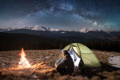 Male tourist have a rest in his camping in the mountains at night under beautiful night sky full of stars and milky way Royalty Free Stock Images