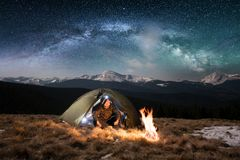 Male tourist have a rest in his camping in the mountains at night under beautiful night sky full of stars and milky way. Male tourist have a rest in his camping Royalty Free Stock Photos