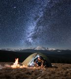 Male tourist have a rest in his camping in the mountains at night under beautiful night sky full of stars and milky way. Male tourist have a rest in his camping Royalty Free Stock Photo