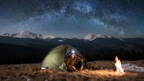 Male tourist have a rest in his camping in the mountains at night under beautiful night sky full of stars and milky way. Male tourist have a rest in his camping Stock Photography