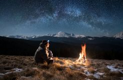 Male tourist have a rest in the mountains at night under beautiful night sky full of stars and milky way. Male tourist have a rest in the mountains at night. Man Stock Photo