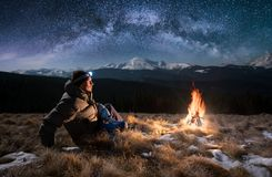 Male tourist have a rest in the mountains at night under night sky full of stars and milky way, and enjoying night scene. Male tourist have a rest in the Royalty Free Stock Images