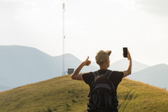 Male tourist on hiking trip happy to receive mobile network connection. Young man on vacation in mountains lifts thumb up and holds cell phone near the cell Stock Photos