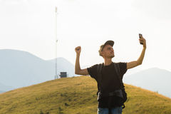 Male tourist on hiking trip happy to receive mobile network connection. Young person spending vacation in mountains holding cell phone near the cell network Royalty Free Stock Image