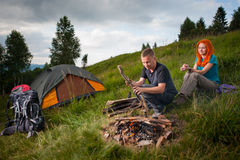 Male tourist on the hill throws wood in the campfire. Young male tourist on the hill throws wood in the campfire, next on the green grass sitting the red-haired Stock Images
