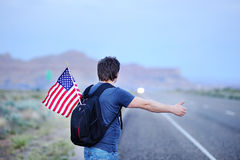Male tourist hitchhiking along a desolate road. Middle age male tourist with american flag in backpack hitchhiking along a desolate road Royalty Free Stock Photo