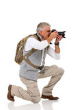 Male tourist knee. Male tourist on his knee taking pictures on white background Royalty Free Stock Images