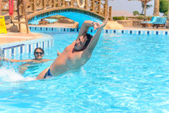 Male tourist launching himself into a pool Royalty Free Stock Images