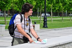 Male tourist with long dark hair. Is oriented in the city on the map Stock Photo