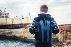 Male tourist looking at an abandoned ship on the sea or ocean back view. Adventure and tourism concept. Male tourist looking at an abandoned ship on the sea or Stock Images