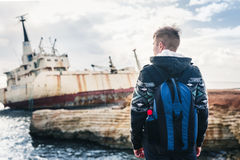 Male tourist looking at an abandoned ship on the sea or ocean back view. Adventure and tourism concept. Stock Photo