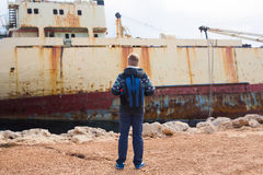 Male tourist looking at an abandoned ship on the sea or ocean back view. Adventure and tourism concept Stock Images